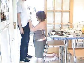 older woman giving fellatio in the kitchen
