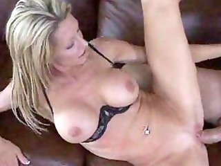older blond sits down on soft couch and copulates